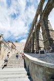 Tourist climb on ancient Aqueduct of Segovia. SEGOVIA, SPAIN - JULY 10, 2011: tourist climb on ancient Aqueduct of Segovia on Plaza del Azoguejo. It consists of stock photography