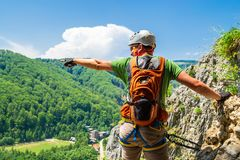 Tourist climber pointing his hand into distance on a via ferrata route in Baia de Fier, Gorj county, Romania. Male climber equipped with helmet, climbing royalty free stock photos