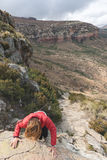 Tourist climbing cliff in the Golden Gate Highlands National Park, South Africa. Adventure and exploration in Africa. Royalty Free Stock Photo