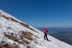 A climbing on a snowy slope. Tourist climbing on a snowy slope to the top of the mountain Stock Photography
