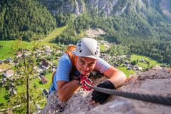 Tourist climbing the via ferrata route Echernwand above Hallstatt, Austria, with houses low on the ground as background. On an afternoon summer day, during a stock images