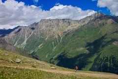 The tourist climbs the trail uphill, the North Caucasus mountain Stock Image