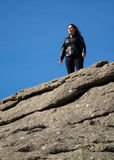 Tourist climbs up the granite slopes of Haytor Rocks Royalty Free Stock Photo