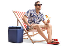 Tourist with a cocktail sitting in a deck chair next to a coolin Royalty Free Stock Image