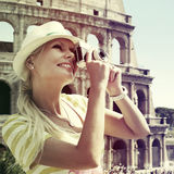 Tourist and Coliseum, Rome. Cheerful Blonde Woman with Camera Royalty Free Stock Photo