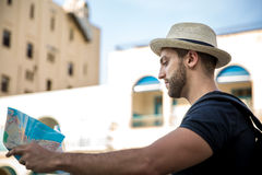 Tourist consulting a city guide searching locations in the street.  Stock Image