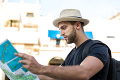 Tourist consulting a city guide searching locations in the street.  Stock Photo