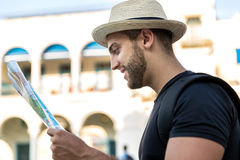 Tourist consulting a city guide searching locations in the street Royalty Free Stock Image