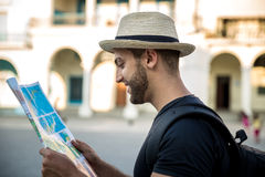 Tourist consulting a city guide searching locations in the street.  Royalty Free Stock Images