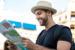 Tourist consulting a city guide searching locations in the street.  Stock Photos