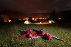 Tourist couple admiring the night sky and lying on the grass Royalty Free Stock Images