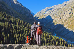 Tourist couple in Ala-Archa valley, Kyrgyzstan. The image of young couple in mountain landscape of Ala-Archa valley in the earlier summer's morning, Kyrgyzstan Stock Photo