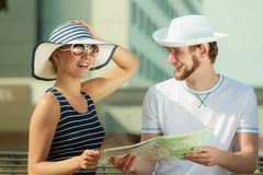 Tourist couple in city looking up directions on map Stock Photography