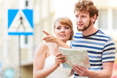 Tourist couple in city looking up directions on map. Summer travel concept. Young tourist couple on vacation city street looking up directions on map royalty free stock image