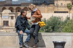 Tourist couple in Cordoba in front of the Bridge`s Gate and the Mosque royalty free stock images