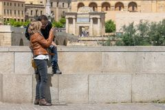 Tourist couple in Cordoba in front of the Bridge`s Gate and the Mosque stock image