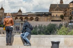 Tourist couple in Cordoba in front of the Bridge`s Gate and the Mosque stock photo
