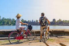 Tourist couple cycling in Angkor temple, Cambodia. Angkor Wat main facade reflected on water pond. Eco friendly tourism traveling.  royalty free stock images