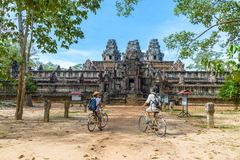 Tourist couple cycling around Angkor temple, Cambodia. Ta Keo building ruins in the jungle. Eco friendly tourism traveling.  stock photos