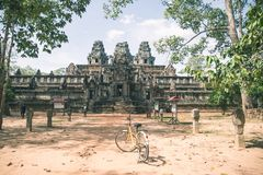 Tourist couple cycling around Angkor temple, Cambodia. Ta Keo building ruins in the jungle. Eco friendly tourism traveling royalty free stock photography