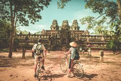 Tourist couple cycling around Angkor temple, Cambodia. Ta Keo building ruins in the jungle. Eco friendly tourism traveling, toned. Image stock photo