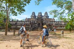 Tourist couple cycling around Angkor temple, Cambodia. Ta Keo building ruins in the jungle. Eco friendly tourism traveling, toned royalty free stock photos