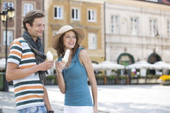 Tourist couple enjoying ice cream cones during vacation Royalty Free Stock Photos