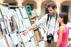 Tourist couple in Havana, Cuba. Looking at books together having fun on vacation travel on Plaza de Armas in Old Havana. Young travelers interracial couple Stock Photography