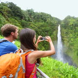 Tourist couple on Hawaii taking pictures. Of the famous Akaka Falls waterfall on Hawaii, Big Island, USA. Happy cheerful young multicultural couple tourists on Stock Photography