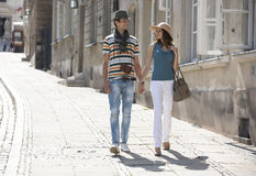 Tourist couple holding hands while walking on sidewalk Royalty Free Stock Image