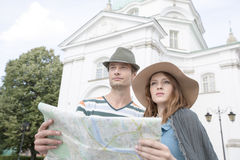 Tourist couple holding map outside St. Casimir Church, Warsaw, Poland Royalty Free Stock Image
