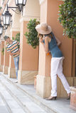 Tourist couple looking at each other while hiding behind columns Stock Photos