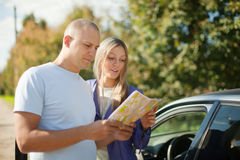 Tourist couple looking at the map on road. Tourist couple looking at the map on the road. Focus on woman royalty free stock image