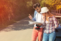 Tourist couple looking at the map on the road. Royalty Free Stock Photo