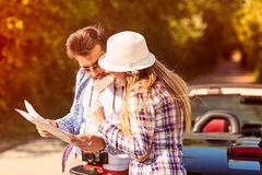 Tourist couple looking at the map on the road. Stock Photos