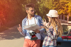 Tourist couple looking at the map on the road. Royalty Free Stock Photography