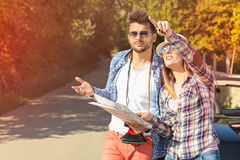 Tourist couple looking at the map on the road. Royalty Free Stock Images