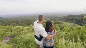 Tourist couple looking on mountain and highlands covered green forest on skyline background. Traveling couple embracing stock footage