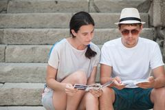 Tourist couple in love enjoying city sightseeing. Sitting on the stairs in the fortress Stock Image