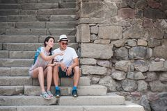 Tourist couple in love enjoying city sightseeing. Sitting on the stairs in the fortress Stock Images