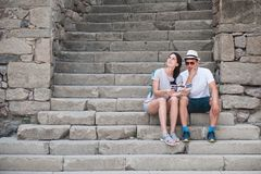 Tourist couple in love enjoying city sightseeing. Sitting on the stairs in the fortress Stock Photography