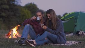 Tourist couple in love with phone near camping in nature. Tourist couple in love looking at mobile phone, having romantic getaways near camping in nature stock video
