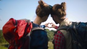 Tourist couple in love traveling, making heart sign with hands. Tourist couple in love traveling with travel backpacks, making heart sign with hands while stock footage