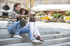Tourist couple photographing on steps stock photo