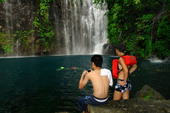 Tourist couple photographing tropical waterfall. Asian couple taking photos on their cellphone camera of a tropical waterfall with a pond in a pristine rain Stock Photo