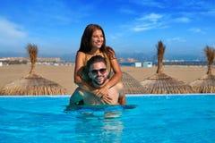 Tourist couple piggyback in infinity pool Stock Image