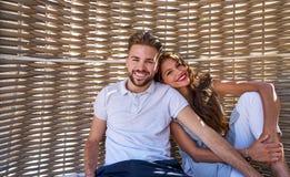 Tourist couple relaxed inside a beach parasol Stock Photos
