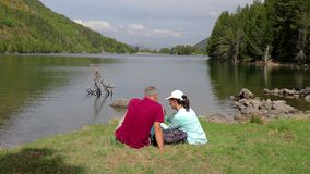 Tourist couple sitting next to the mountain lake and take a picture with mobile phone.  stock video