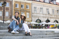 Tourist couple sitting on steps against building Stock Photography