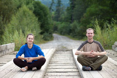 Tourist couple sitting on a wooden bridge Stock Images